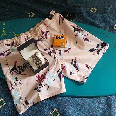Swimming shorts, skimboard and wax