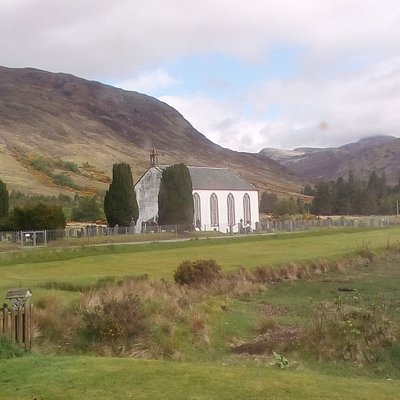 The church with the bald red head mountain behind, from the golf course cafe
