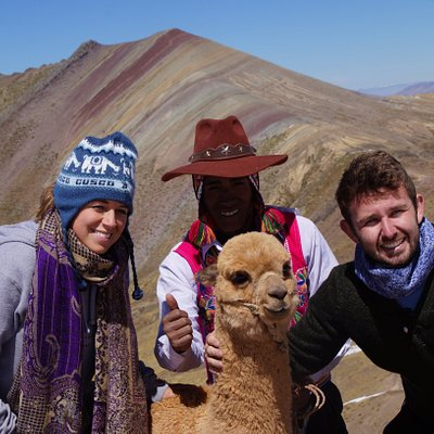 posing right across the rainbow mountain along with llama and local person.