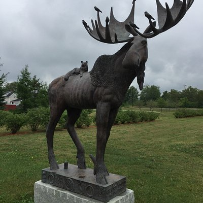 A life-size bronze moose statue has be accessorized with a Maine Coon Cat, lobsters, a can of Mo