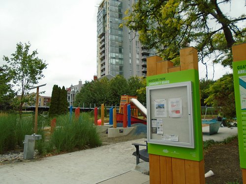 Playground area and noticeboard. Railway in background
