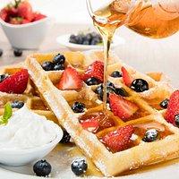 Waffles con frutos rojos, miel de maple y crema chantilly