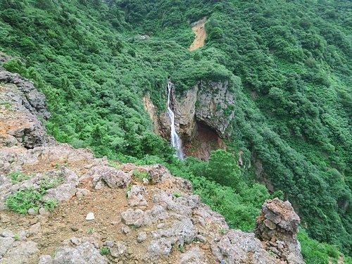 山の崖に滝が流れている
