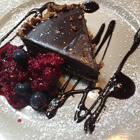 Dessert of fresh berries and chocolate mouse-like tort.