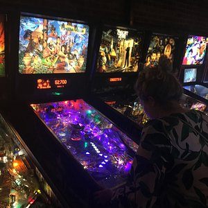 Row of pinball machines in bar area