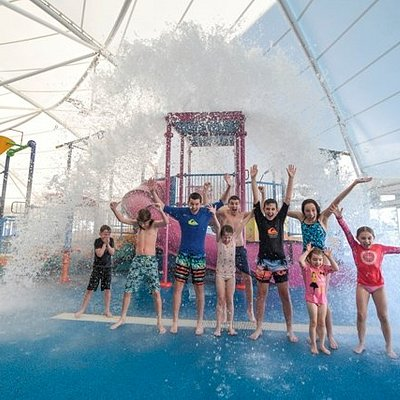 Kids enjoying over 1200 litres of water tipping down from the giant bucket in the splash park!
