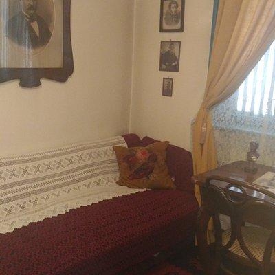 спальня, над кроватью портреты трех русских писателей
