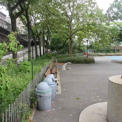 Park area with a basket ball court and benches, it is above the highway