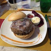 Hamburger farcito di formaggio e cipolle e rivestito da lardo