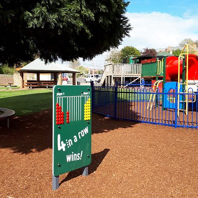 Park includes shady areas, picnic tables, a fenced toddler playground and a train.