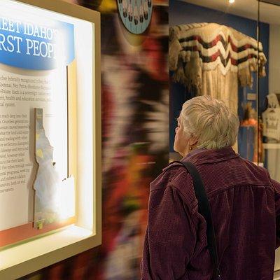 Visitor reading tribal exhibit panel in Origins Gallery
