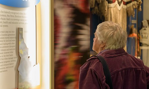 Visitor reading tribal exhibit panel in Origins Gallery