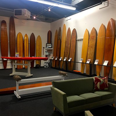 """Main gallery showing vintage wood surfboards and a """"motorized"""" board."""