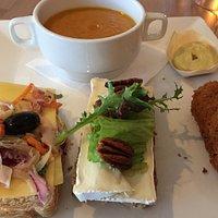 Smakelijke lunch, met pompoensoep, kroketje en twee grappige sneetjes brood.
