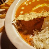 Butter chicken with papadum, basmati rice, and fries.
