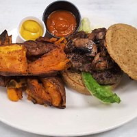 Grass-fed beef burger with gluten-free bun and sweet potato wedges