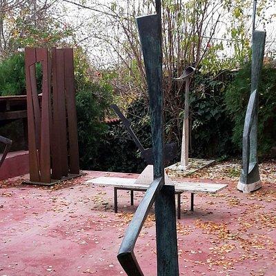"""A Kalmar Art Studió szoborkertjének részlete, a bal felső sarokban Kalmár János szobrászművész  """"Erdő"""" című szoborcsoportjának néhány eleme, elöl a 2 m-nél valamivel magasabb  """"Sitting Man"""" """"Ülő ember"""" című szobor, mögötte a """"Barbate""""."""