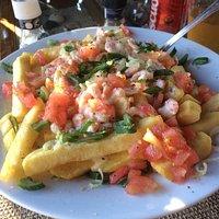 Papas Makona: salsa de queso, camarones, tomate, cebollín y muuchas papas fritas