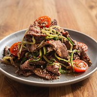 'Crying Tiger' Charcoal grilled South Australian grass-fed beef salad with fresh herbs cucumber 'noodles' and tomato