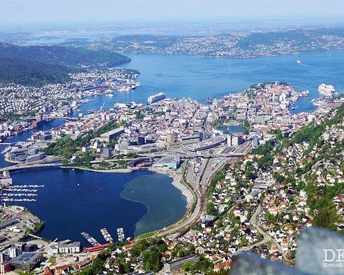"""Blick vom Ulriken auf den Hafen von Bergen und die dort liegenden Kreuzfahrtschiffe.   Ich war im Mai mit der Mein Schiff 4 in Bergen und habe über die Reederei eine Stadtrundfahrt mit Fahrt auf den Ulriken gebucht.  Bei bestem Wetter hatten wir tolle Sicht, standen aber lange an der Seilbahn an.   Wer Näheres zur Reise und/oder zum Ausflug wissen möchte, sollte auf meinem Blog vorbeischauen. Dort gibts den Reisebericht zur Kreuzfahrt """"Südnorwegen mit Kopenhagen"""" und den Artikel zum Landausflug."""