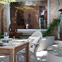 Courtyard seating under a beautiful stinkwood tree, surrounded by exquisite art.  A calm environment in which one can relax, whilst enjoying a meal prepared using local and seasonal produce.
