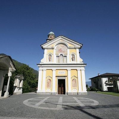 Il sacrato circolare della Chiesa di San Lorenzo con le cappelle della Via Crucis in una giornata di Sole a Losone, nel Locarnese.