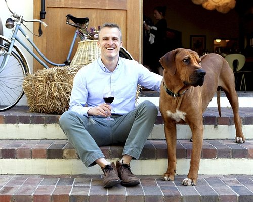 Winemaker Kristopher Tillery with winery dog Kuba at the entrance to the cellar.