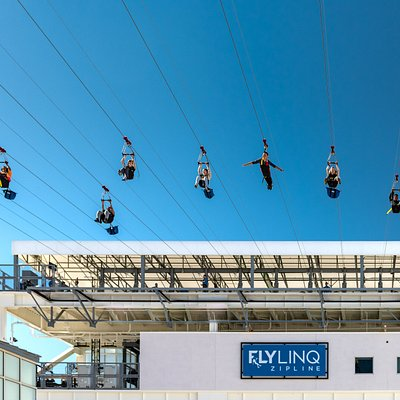 Riders flying down the FLY LINQ Zipline.