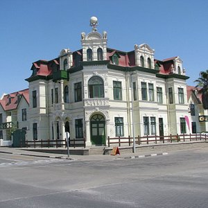 """We offer city tours of Swakopmund which has many histrical buildings dating from the German colonial past. One of the most prominent historical building of that era is the """"Hohenzollern"""" building seen on this picture. It was built in 1905 as a hotel and housed the first town council of Swakopmund. It has been changed to sectional title flats in the meantime and is well preserved."""