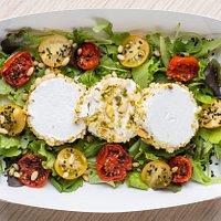 Ricotta in crosta di pistacchi e mandorle con pomodorini confit rossi e gialli su letto di insalata