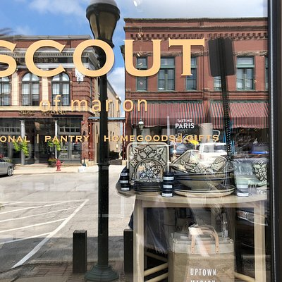 Outside of SCOUT in marion, with the historic buildings across the street reflected in the window.