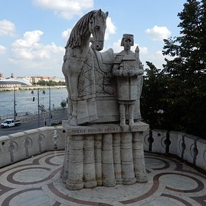 Stone statue of King Saint Stephen in front of his horse and holding a model of a church