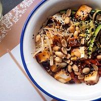 Tagliolini di soia con peperoni e zucchine, germogli di soia, tofu caramellato, arachidi, salsa al latte di cocco e semi di sesamo