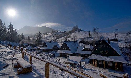 Penzión Jánošíkov dvor v zimnom období. Pohľad zo zasneženého golfového ihriska.