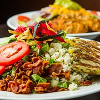 Sante Fe Cobb Salad: Romaine lettuce, diced tomatoes, avocado, bacon, gorgonzola, diced egg, corn, black beans, tortilla strips, grilled chicken. Served with chipotle ranch dressing