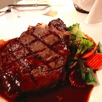Black Angus Ribeye topped with rosemary red wine demi glace, roasted rosemary potatoes and seasonal vegetables