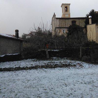vista laterale della chiesa di San Pastore, in inverno con la neve