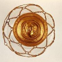 Un  antichissimo  e prezioso gioiello di epoca  ellenistica *  romana , in oro purissimo -  la cui inestimabile bellezza è  data dal volto cesellato  con innegabile perizia , altrettanto mirabile  la rete catenaria, sempre  in oro ,destinata  ad  adornare la capigliatura  di  una  sconosciuta matrona.