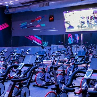 Sala de spinning con pantalla y bicicletas de ciclismo indoor.