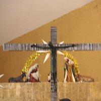 Imagen del cristo crucificado con el belén navideño al fondo.