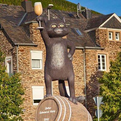 """Für die Weine aus der Großlage """"Zeller Schwarze Katz"""" wurde die Weinstadt Zell (Mosel) weltbekannt. Das Wahrzeichen der Stadt thront auf dem Kreisverkehr am Ortseingang und begrüßt Besucher aus Nah und Fern mit erhobenem Weinglas."""