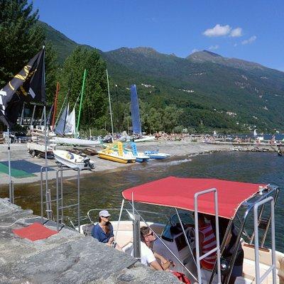 Blick auf das Tomaso Sail & Surf Wassersport Center am Lido in Cannobio von der An- und Ablege-Mole für Motorboote