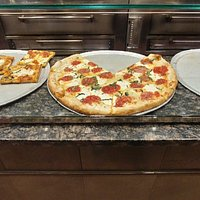 Look at all of these specialty pizzas at the counter.