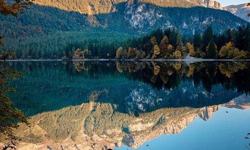 Un'alba da sogno sul lago di Tovel, in Val di Non, Trentino. Consiglio di arrivare sul luogo presto al mattino per poter trovare il luogo di scatto migliore e ottenere dei riflessi perfetti sulla superficie dell'acqua.