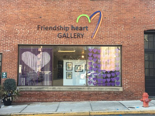 """Friendship Heart Gallery is located across from Miesse Candy in the Steeple View Lofts building on Water Street. The month of February is the exhibit titled, """"Lean on Me"""", which features playful pairs and thoughts of love, friendship and companionship. The window display for February features an interactive heart activity in which you can write on your own heart for others to see."""