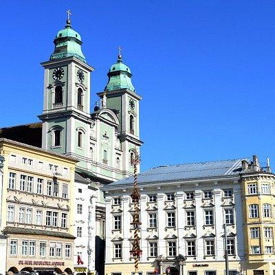 """Hauptplatz met gevels aan de zijde van de oude  Dom,  met de voorgevel en toren van deze """"Oude Dom"""" en ook een een deel van de meiboom."""