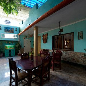 Area del primer nivel, techada, con jardines y mesas para servir desayunos y cenas donde se encuentran dos habitaciones.