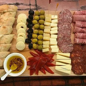 Picada board - stuffed olives, cheese, meets, garlic oil, peppers, hearts of palm, toasted baguette.