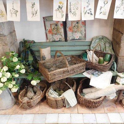 Anciennes planches lithographiées de fleurs, vieux paniers en osier, toiles à torchons en métis, pots de fleurs vernissés...