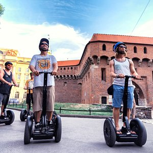 Tourist on Segways with Barbakan behind